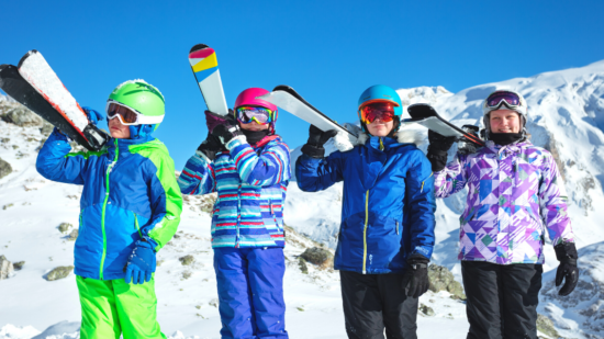 Children dressed in full ski gear with helmets in front of snow covered mountain